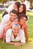 Multi Generation Family Lying In Pile Up On Grass Together Royalty Free Stock Images