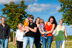 Multi-generation family on meadow in summer. Family and multi-generation - mother, father, children and grandmother having fun on meadow in summer Stock Photo