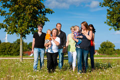 Multi-generation family on meadow in summer. Family and multi-generation - mother, father, children and grandmother having fun on meadow in summer Stock Images
