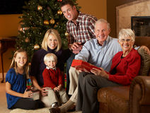 Multi Generation Family Opening Christmas Presents. In Front Of Tree Smiling To Camera Stock Photography