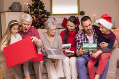 Multi generation family opening gifts on sofa Stock Photos