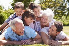 Multi Generation Family Piled Up In Garden Together Stock Photos