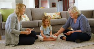 Multi-generation family playing cards in living room 4k stock video footage