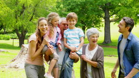 Multi generation family posing and laughing at camera in a park Royalty Free Stock Image