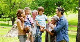 Multi generation family posing and laughing at camera in a park Stock Photos