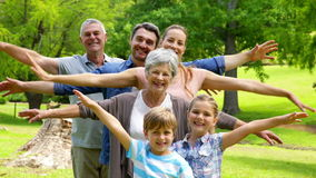 Multi generation family posing and smiling at camera in a park Royalty Free Stock Photo
