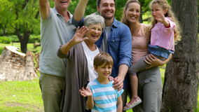 Multi generation family posing and waving at camera in a park Royalty Free Stock Images