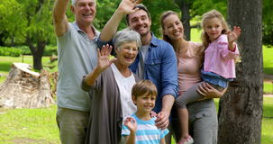 Multi generation family posing and waving at camera in a park Stock Photo