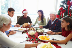 Multi Generation Family Praying Before Christmas Meal. Sitting Around Table Holding Hands Royalty Free Stock Photos