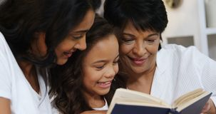 Multi-generation family reading a book in bedroom 4k. Multi-generation family reading a book in bedroom at home 4k stock video footage