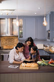 Multi-generation family reading book together in kitchen Stock Photography