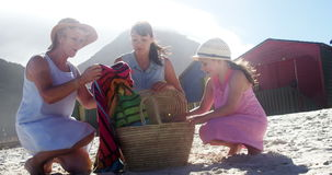 Multi generation family removing towel from picnic basket stock video footage