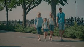 Multi generation family resting in nature. Happy multi generation family with adorable elementary age girl enjoying walk along park alley while relaxing together stock footage