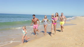 Multi Generation Family Running Along Beach Royalty Free Stock Photos