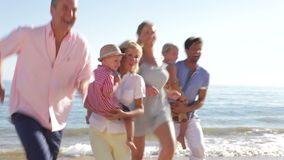 Multi Generation Family Running Along Beach Stock Photography