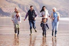 Multi Generation Family Running On Winter Beach Royalty Free Stock Photos
