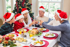 Multi generation family in santa hat toasting each other Stock Photography