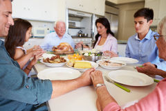 Multi-Generation Family Saying Prayer Before Eating Meal Stock Image