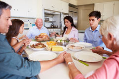 Multi-Generation Family Saying Prayer Before Eating Meal. Holding Hands With Eyes Closed stock photos