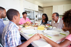 Multi-Generation Family Saying Prayer Before Eating Meal. In Kitchen Royalty Free Stock Photography