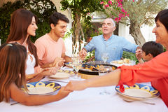 Multi Generation Family Saying Prayer Before Meal Together Stock Photo