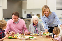 Multi-generation family sharing meal together. At home in kitchen Stock Photography