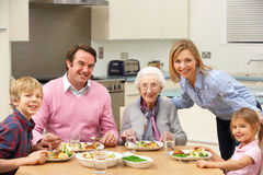 Multi-generation family sharing meal together. Smiling at camera Royalty Free Stock Images