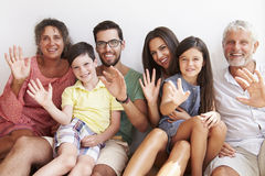 Multi Generation Family Sitting Against Wall And Waving Stock Photo