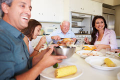Multi-Generation Family Sitting Around Table Eating Meal stock image