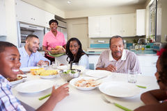 Multi-Generation Family Sitting Around Table Eating Meal Royalty Free Stock Photo