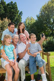 Multi generation family sitting on a bench taking photo of thems Stock Image