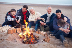 Multi Generation Family Sitting By Fire On Winter Beach royalty free stock photo