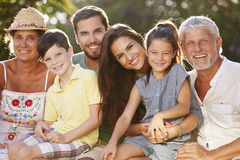 Multi Generation Family Sitting In Garden Together royalty free stock photography