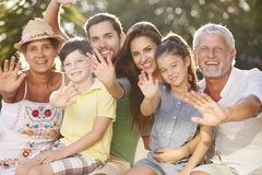 Multi Generation Family Sitting In Garden And Waving Stock Photo