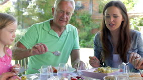 Multi-Generation Family Sitting Outdoors Around Table Eating stock video footage