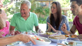 Multi-Generation Family Sitting Outdoors Around Table Eating