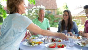 Multi-Generation Family Sitting Outdoors Around Table Eating stock video