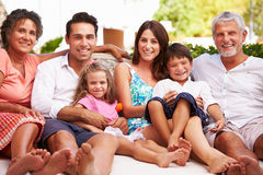 Multi Generation Family Sitting Outdoors At Home Together stock images