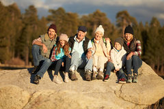 Multi generation family sitting on rocky outcrop near a forest Royalty Free Stock Images