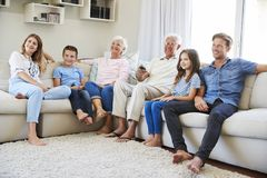 Multi Generation Family Sitting On Sofa At Home Watching TV royalty free stock photography