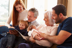 Multi Generation Family Sitting On Sofa With Newborn Baby Stock Photo