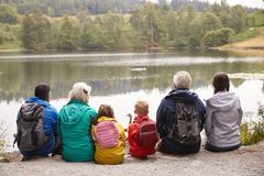 Multi generation family sitting together admiring the view on the shore of a lake, back view, Lake District, UK stock photo