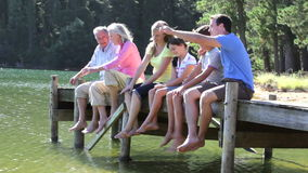 Multi-Generation Family Sitting On Wooden Jetty By Lake stock video