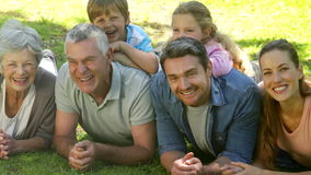 Multi generation family smiling and lying on ground in a park Stock Photos