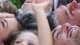 Multi generation family smiling and lying on ground in a park waving up Royalty Free Stock Photography