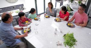 Family Enjoying a Stir Fry Dinner Together. Multi generation family socialising over a stir fry dinner together stock footage