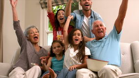 Multi generation family on the sofa cheering while watching television stock video