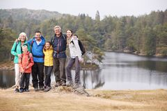 Multi generation family stand embracing by a lake, smiling to camera, front view, Lake District, UK stock image