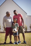 Multi-generation family standing in garden with football. Happy multi-generation family standing in garden with football Royalty Free Stock Image