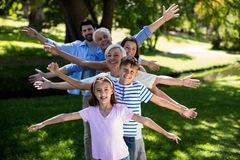 Multi generation family standing in a row with arms outstretched Royalty Free Stock Photos